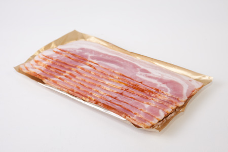 Bacon slices on the package, isolated on white background photo