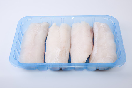 hake: Boneless hake steaks placed on their plastic tray. Isolated over white background