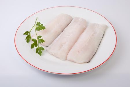 Boneless hake steaks on plate with parsley