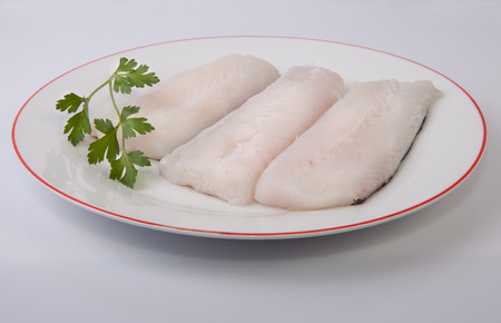 hake: Boneless hake steaks on plate with parsley