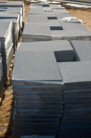 Stacks of concrete tiles on wooden palete in construction site