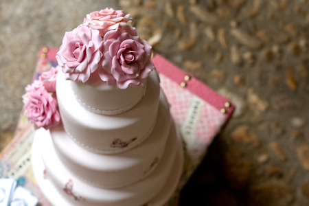 cake tier: Fondant wedding cake with pink roses over vintage suitcase Stock Photo
