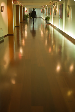 Woman walking by a hotel corridor with wooden floor photo