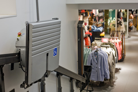 maschine: Chair lift for disabled and elderly people to climb stairs in a clothing store Stock Photo