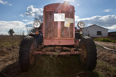 Front view of rusty vintage tractor on farmland, Badajoz, Spain photo