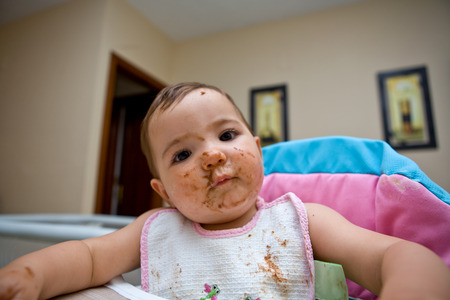 highchair: A baby girl eating chocolate biscuits on her highchair. Fourteen months old Stock Photo