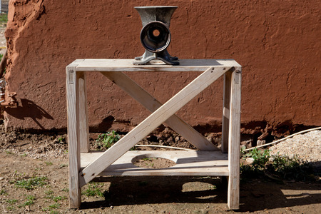 slaughtering: Manual mincer machine over wooden stand. Traditional home slaughtering in a rural area, Extremadura, Spain