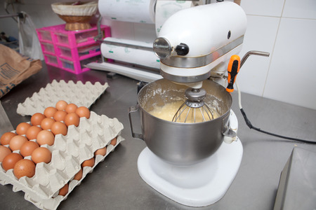churning: Churning mass in confectionery machine. Manufacturing process of spanish madeleines
