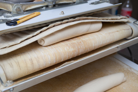 moulder: Dough divider and moulder machine at work. Manufacturing process of spanish bread Stock Photo