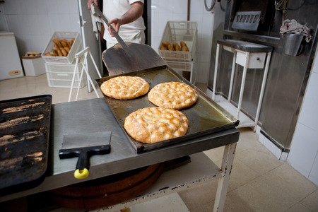 elaboration: Elaboration process of traditional spanish olive oil pancakes. Baker taking fresh baked pancakes from oven Stock Photo
