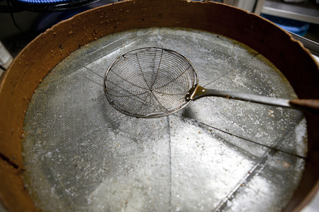 cooking oil: Skimmer driping oil over sieve. Used for cooking with fried food