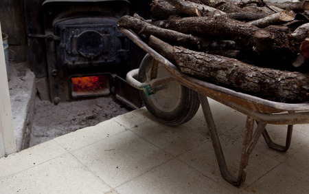 backdoor: Old wheelbarrow full of holm oak firewood close to bakery oven backdoor. Manufacturing process of spanish bread