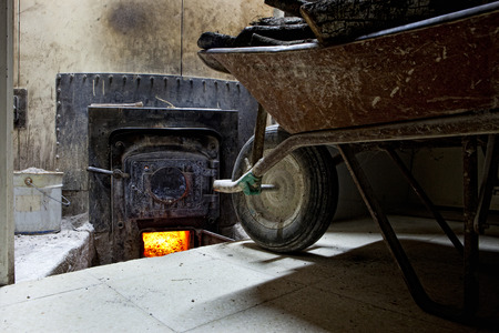 bakery oven: Old wheelbarrow full of holm oak firewood close to bakery oven backdoor. Manufacturing process of spanish bread