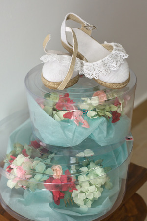 footstool: Floral white bridal headdress and shoes on their boxes over wooden footstool