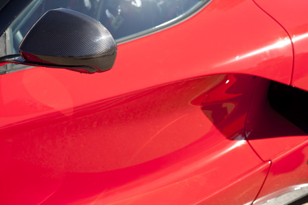 red sports car: Red sports car wing mirror. Detail of a luxury car