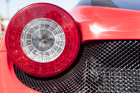red sports car: Red sports car spot light. Detail of a luxury car