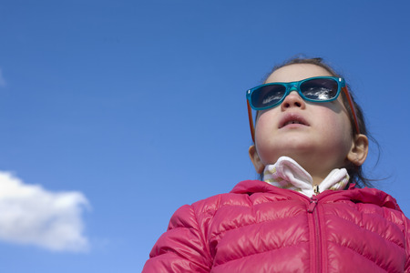 2 5: Portrait of cute 2,5 years old toddler girl with fashion children sunglasses with coat over blue sky with clouds background
