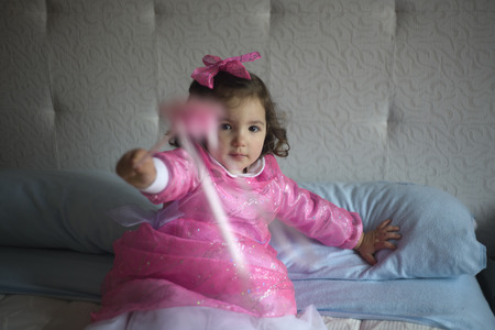 costumed: Little girl costumed as a fairy with magic wand sitting on the bed and playing
