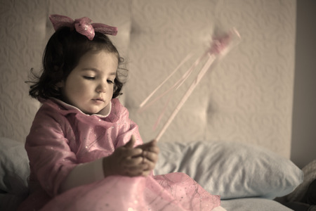 girl magic wand: Little girl costumed as a fairy with magic wand sitting on the bed and playing