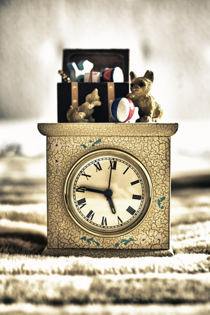 lateness: Old children alarm clock decorated with figurines. Isolated over bed blanket