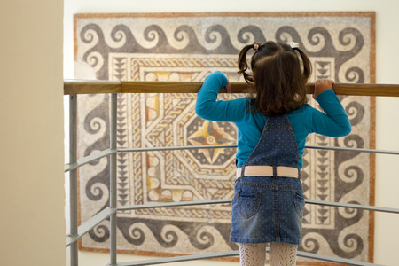 polychrome: Toddle at museum room observing a roman polychrome mosaic of Century VI AC with geometrical shapes Stock Photo