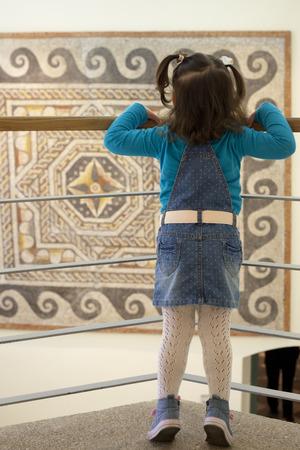 Toddle en la sala museo observando un mosaico policromado romano del siglo VI AC con formas geométricas