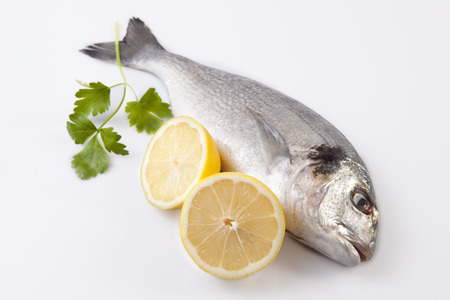 sparus: Raw sea bream fish with some ingredients. Isolated over white background