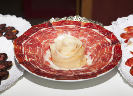 iberico: Plate full of spanish cured iberico ham slices with a rolled strip of fat as a rose in the middle