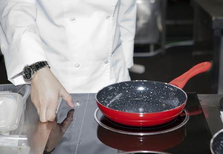 cooktop: A woman hand turn the fire on just before cooking with a red pan
