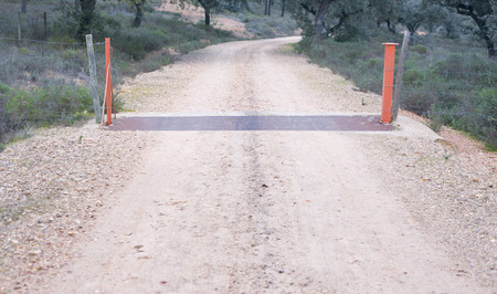 cattle guard: A cattle grid in a dirt track at dehesa landscape Extremadura Spain