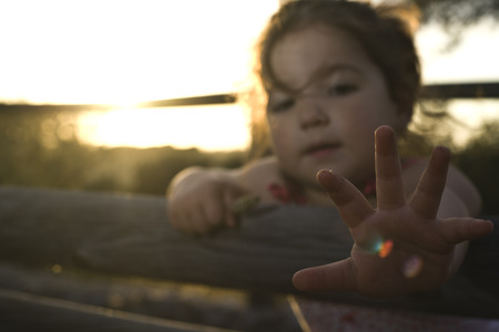 extremadura: Adorable toddler smiling girl playing in the dehesa field Extremadura. Magic back light. Sunset