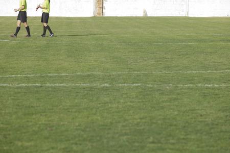 arbitros: Dos �rbitros de f�tbol, ??un hombre y una mujer caminando por el campo Foto de archivo