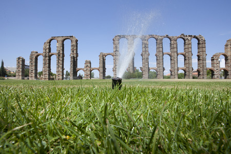 buttresses: Grass Sprinklers wtih Roman Aqueduct of Merida at the bottom. Extremadura, Spain