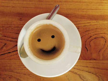 Taza de café con la cara sonriente sobre superficie de madera