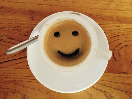 invigorate: Coffee cup with smiley face over wooden surface