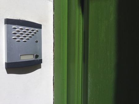 intercom: Old intercom over whitewashed wall, beside green wooden door