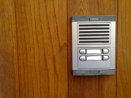 intercom: Intercom over golden wooden door with two buttons Stock Photo