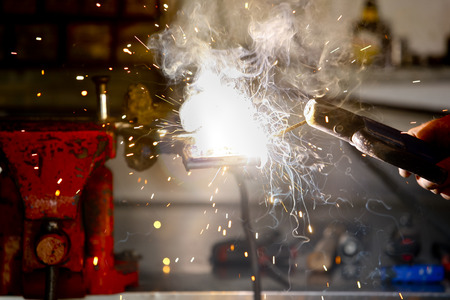 Stick welding worker in action with no protection gloves Stock Photo