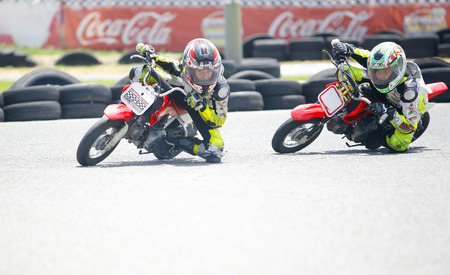 mini bike: MARBELLA - JUL 5: kids riding freestyle Motocross bikes on asphalt. Junior competition training at Funny Beach circuit on July 5, 2015 in Marbella, Spain