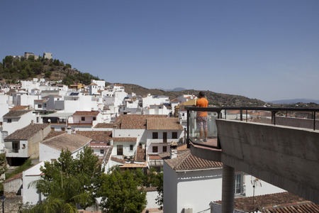 observes: Tourist observes from viewpoint the town rooftops towards the mountains. Monda, Andalusia, Spain, Western Europe Stock Photo
