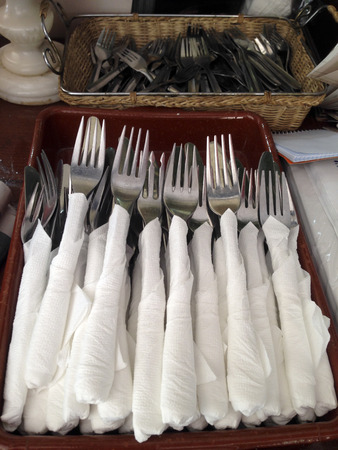 serwetki: Baskets of forks covered with paper napkins