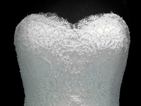 neckline: Wedding dress with heart neckline on a mannequin over black background