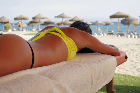 gstring: Massage area on the beach with suntanned beautiful woman lying down on summer vacation season Stock Photo