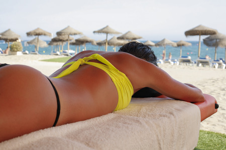 tanga: Massage area on the beach with suntanned beautiful woman lying down on summer vacation season Stock Photo