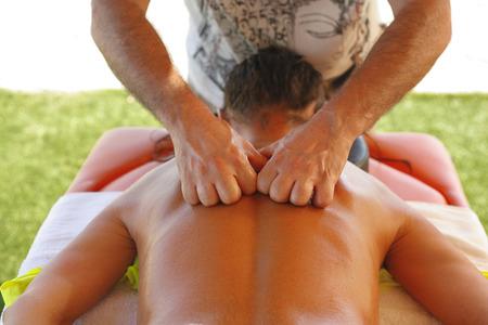 suntanned: Massage therapist working with suntanned beautiful woman at  beach resort