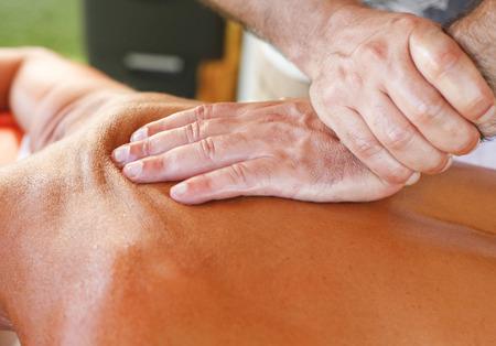 Terapeuta del masaje que trabaja con la mujer hermosa bronceada en el centro turístico de playa