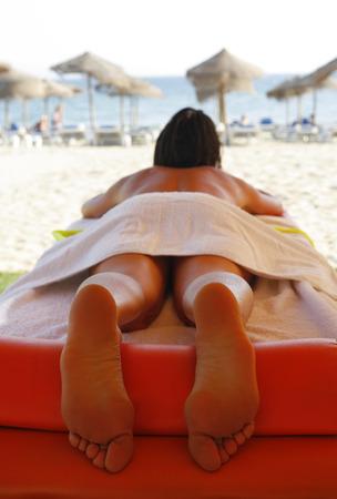 suntanned: Massage area on the beach with suntanned beautiful woman lying down on summer vacation season Stock Photo