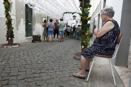 campo: CAMPO MAIOR, PORTUGAL -23 AUGUST 2015: Flower festival in Campo Maior. A woman is sitting beside her house at decorared streets, on 23 August 2015 Campo Maior,  Portugal