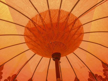 thai craft: Interior of orange traditional Thai umbrella, craft against the sunlight Stock Photo