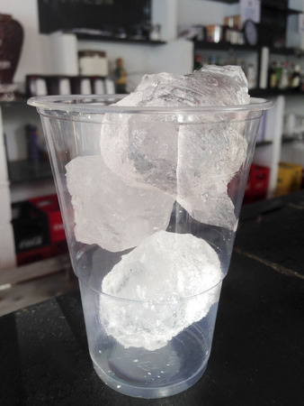 over the counter: Takeaway cup full of ice over on black counter of a bar Stock Photo